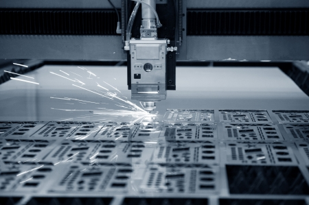 machine: Industrial laser cutter with sparks.