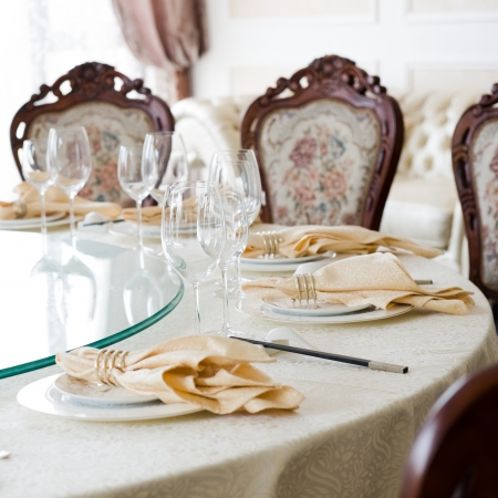 formal dinner party: Formal dining room table and chairs set for dinner