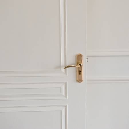 modern style door handle on white wooden door. photo