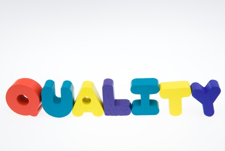 Wooden letters spelling the word   quality   on white background.  photo