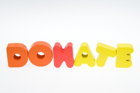 contribute: Wooden letters spelling the word   donate   on white background.
