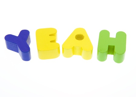 yeah: Wooden letters spelling the YEAH  on white background.  Stock Photo