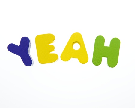 yeah: Wooden letters spelling the word  YEAH  on white background.  Stock Photo