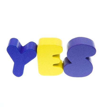 Wooden letters spelling the word  YES  on white background. Stock Photo - 14588464