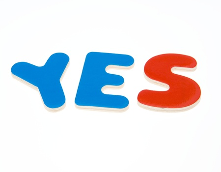 Wooden letters spelling the word  YES  on white background.  Stock Photo - 14588307