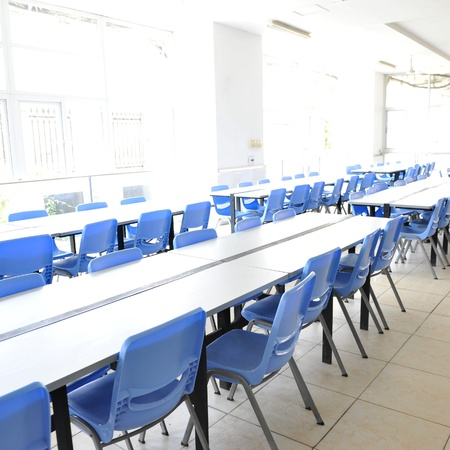 Clean school cafeteria with many empty seats and tables.  Stock Photo