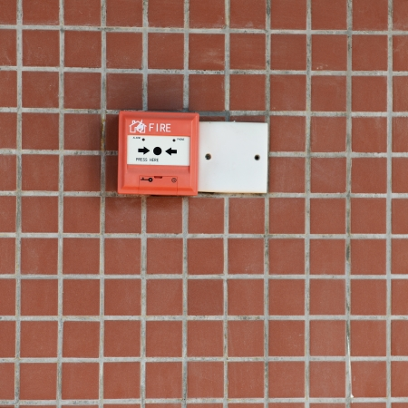 red fire alarm on brick wall  photo