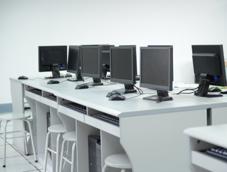 univercity: Rows of computer neatly placed in a computer lab.  Stock Photo