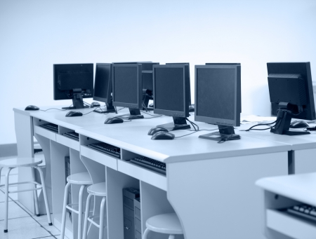 Rows of computer neatly placed in a computer lab.  photo