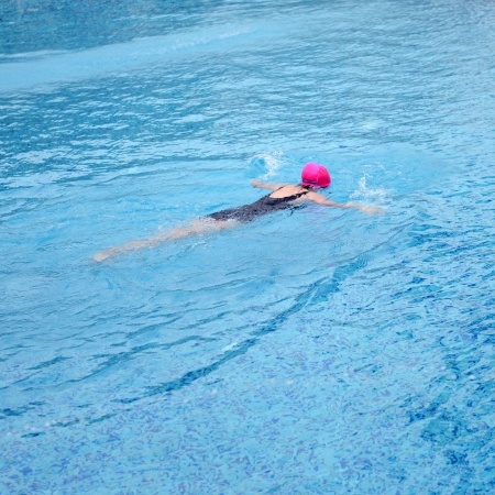 Top view of young woman diving in a swimming pool photo