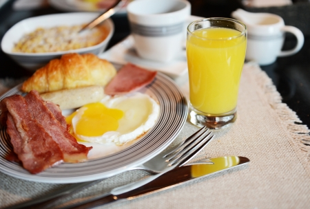 bacon and eggs: Breakfast with bacon, fried egg, orange juice and coffee. Stock Photo
