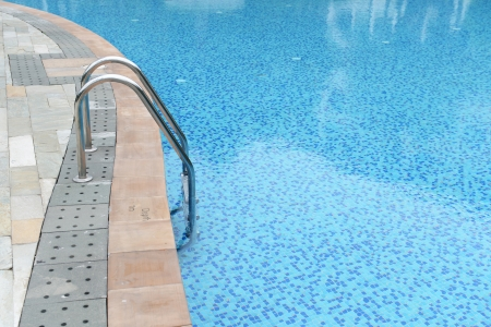 pool deck: blue swimming pool with stair at hotel. Stock Photo
