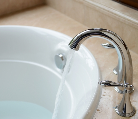 Luxury bath tub and faucet with water.  Stock Photo