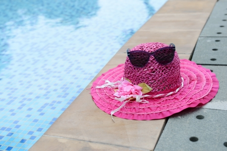 pink hat: A pair of sunglasses and summer hat resting on the side of pool.
