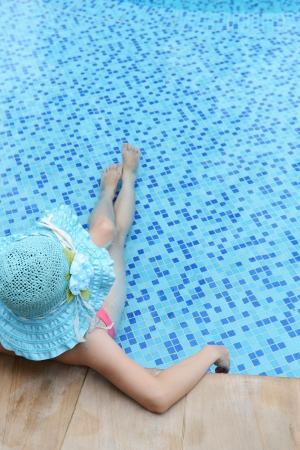 enjoy space: woman enjoying a swimming pool in a large sunhat