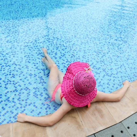 woman enjoying a swimming pool in a large sunhat  photo