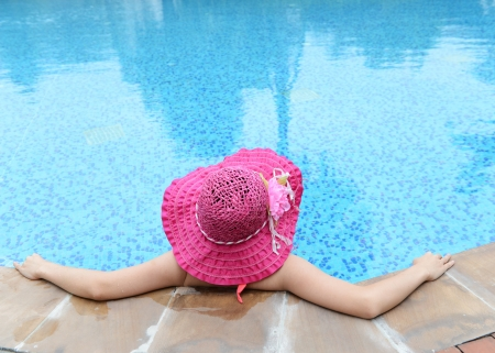 sexy asian girl: woman enjoying a swimming pool in a large sunhat