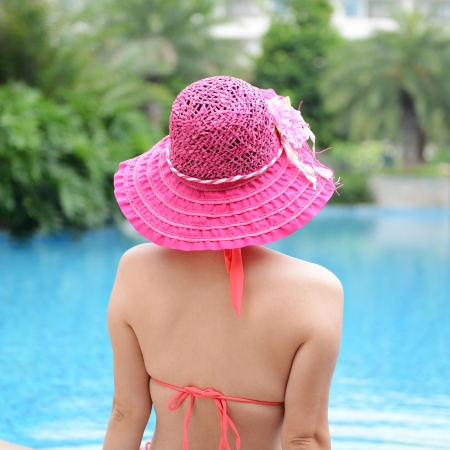 pink hat: Rear view of asian woman relaxing in the swimming pool.