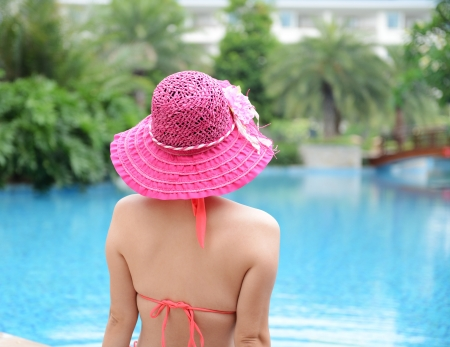 Rear view of asian woman relaxing in the swimming pool. photo