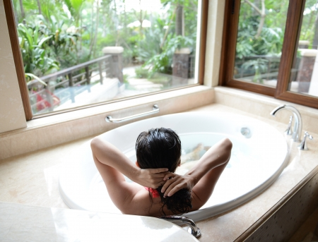 young woman in bathtub with a beautiful view outside the window Stock Photo - 15137031