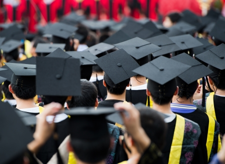 graduate hat: back of graduates during commencement.  Stock Photo