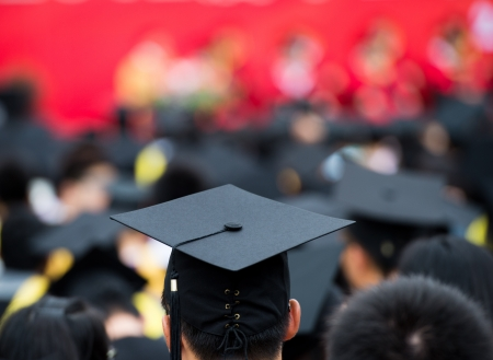black cap: back of graduates during commencement.  Stock Photo