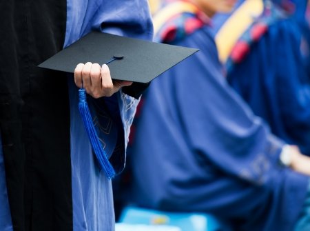 mortarboard: graduating student holding their mortarboard in hand.  Stock Photo