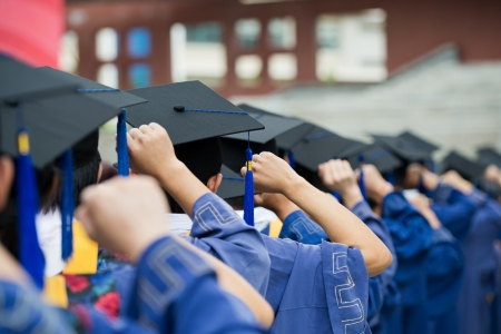 graduacion de universidad: posterior de los graduados poner las manos en alto durante la apertura. Foto de archivo