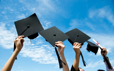 gorros de graduacion: Muchas mano sosteniendo sombreros de graduación en el fondo del cielo azul. Foto de archivo