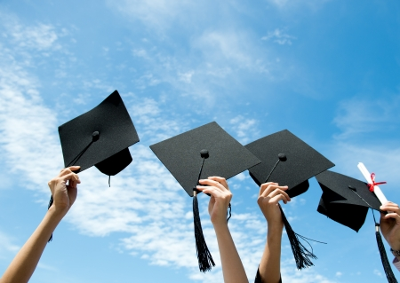 Many hand holding graduation hats on background of blue sky.  Stock Photo