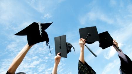 fondo de graduacion: Muchas mano sosteniendo sombreros de graduación en el fondo del cielo azul. Foto de archivo