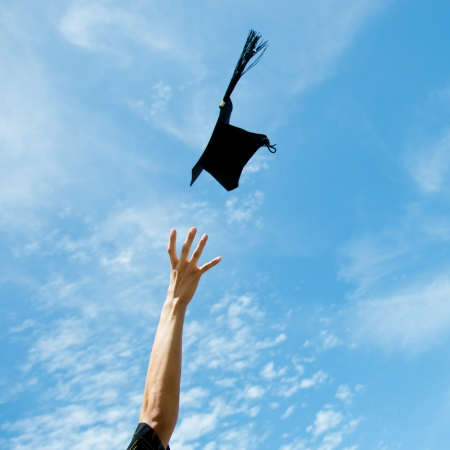 graduates throwing graduation hats in the air.  photo