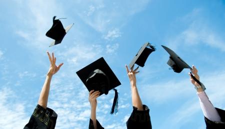 vzdělání: Absolventi házení promoce klobouky do vzduchu. Reklamní fotografie