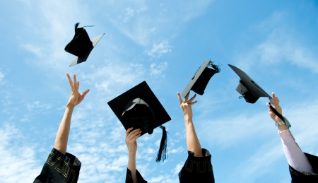 fondo de graduacion: graduados tirando sombreros de graduación en el aire. Foto de archivo