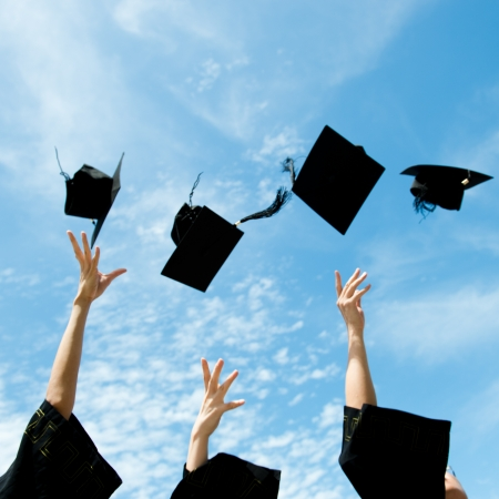 egresado: graduados tirando sombreros de graduaci�n en el aire. Foto de archivo