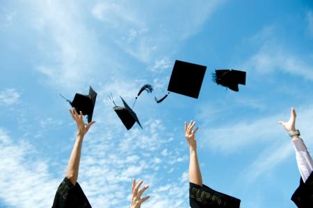 toga y birrete: graduados tirando sombreros de graduación en el aire. Foto de archivo