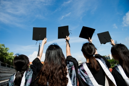 Many hand holding graduation hats on background of blue sky.  photo