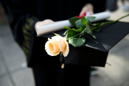 academic achievement: people in a gown holding a diploma and rose. Stock Photo