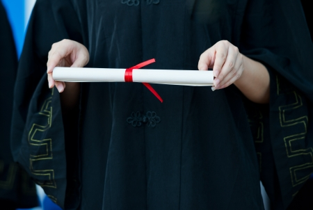 master degree: people in a gown holding a diploma.
