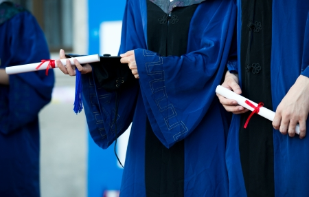 licenciatura: personas en un vestido que sostiene un diploma.