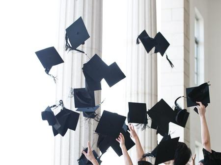 birrete: graduados tirando sombreros de graduación en el aire. Foto de archivo