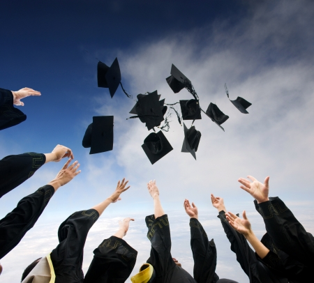 masters degree: high school graduates tossing up hats over blue sky.