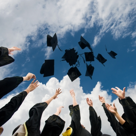graduacion de universidad: bachilleres lanzando hasta sombreros sobre el cielo azul. Foto de archivo