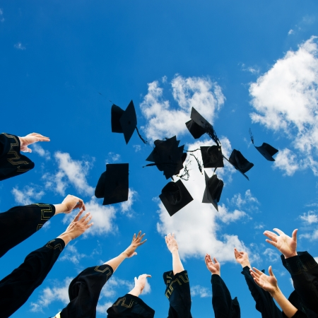 fondo de graduacion: bachilleres lanzando hasta sombreros sobre el cielo azul. Foto de archivo