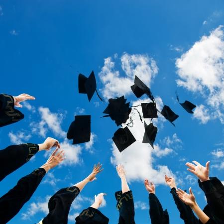 graduation background: high school graduates tossing up hats over blue sky.