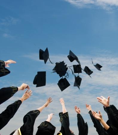 egresado: bachilleres lanzando hasta sombreros sobre el cielo azul. Foto de archivo