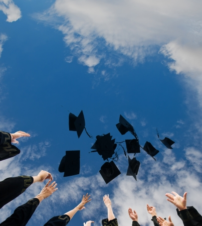 succeed: high school graduates tossing up hats over blue sky.