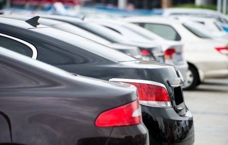 many cars parked in a row.  Stock Photo