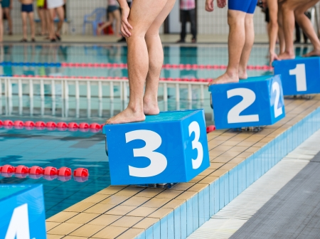 man legs: swimmers on starting block ready to start the swimming race  Stock Photo