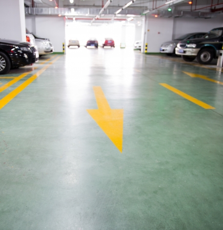 Empty underground garage with arrow leading to go to car park